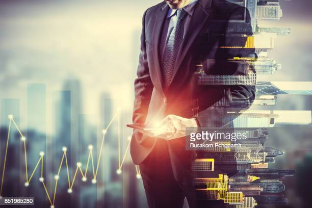 Businessman holding smart phone. Double exposure photo of city view background, Finance strategy concept.