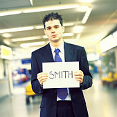 Businessman holding 'Smith' name card in airport, portrait