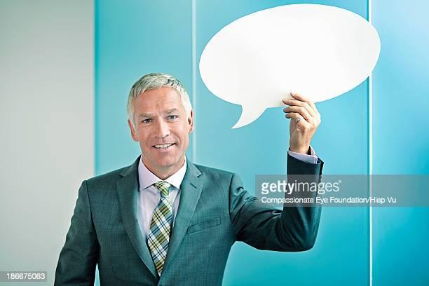 Businessman holding speech bubble