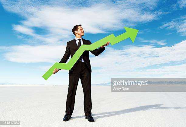 Businessman holding stock arrow on salt flats.