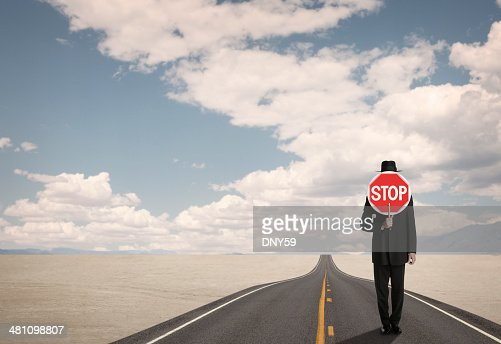 Businessman holding stop sign on remote road in the desert