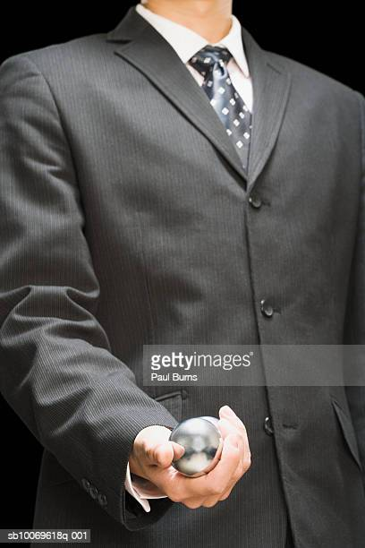 Businessman holding stress ball, mid section