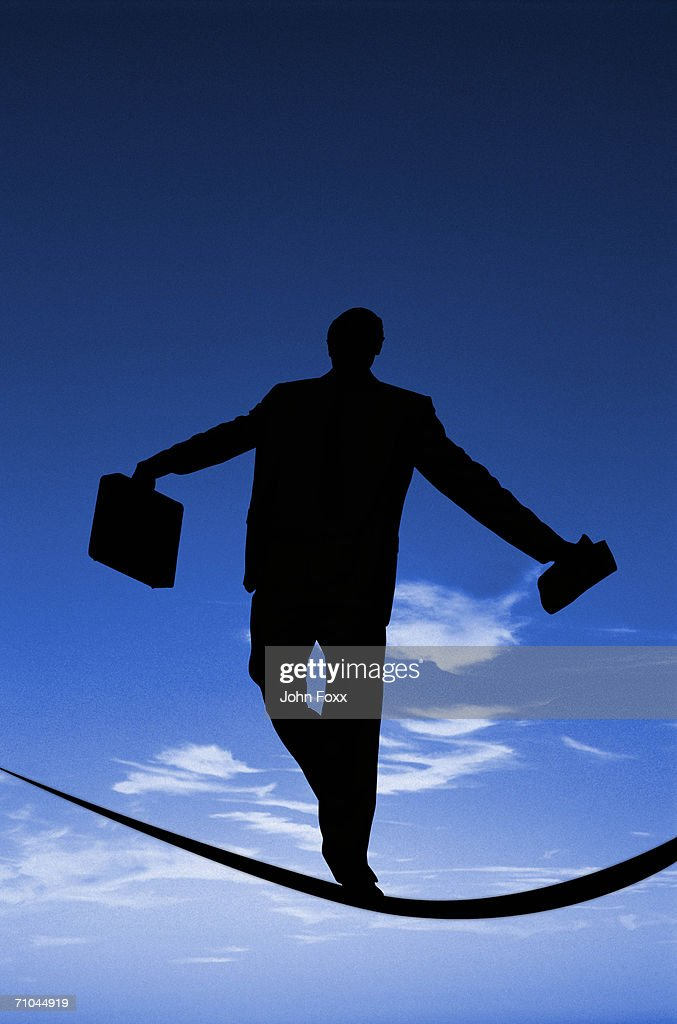 Businessman holding suitcase walking on tightrope, rear view : Stock Photo