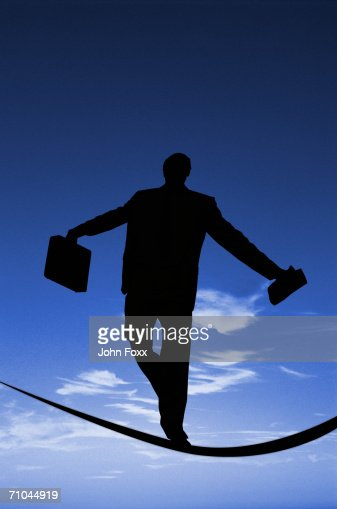 Businessman holding suitcase walking on tightrope, rear view : Foto de stock