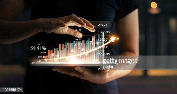 Businessman holding tablet and showing a growing virtual hologram of statistics, graph and chart with arrow up on dark background. Stock market. Business growth, planing and strategy concept. : Stock Photo