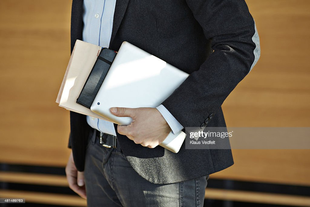 Businessman holding tablet, notebook & newspaper : Stock Photo