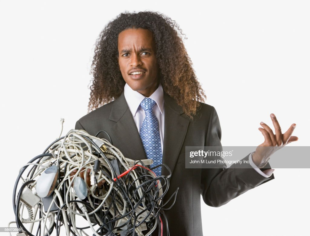 Businessman holding tangled computer cords : Stock Photo