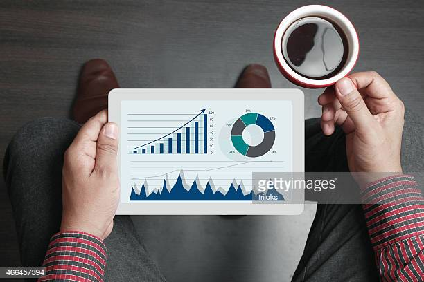 Businessman holding tea cup and digital tablet
