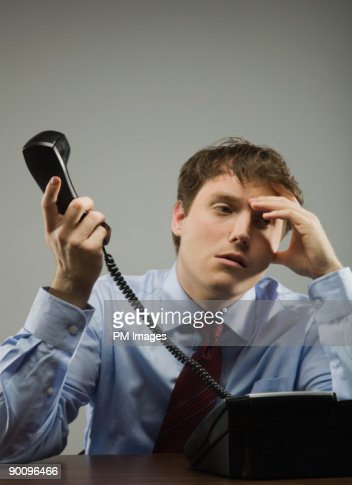 Businessman holding telephone receiver : Stock Photo