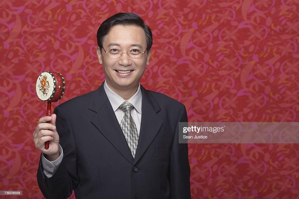 Businessman holding toy drum, portrait : Stock Photo