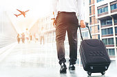 Businessman holding trolley bag going up on travel