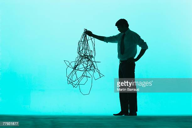 Businessman holding up a pile of cable