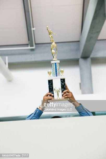 Businessman holding up a trophy