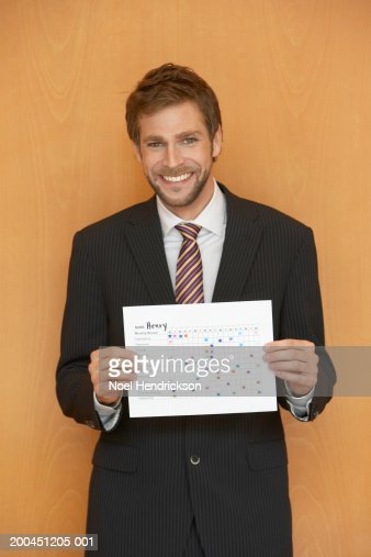 Businessman holding up chart smiling, portrait : Stock Photo