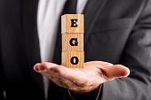 Businessman holding wooden alphabet blocks reading - Ego - balanced in the palm of his hand in a conceptual image.