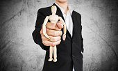 Businessman holding wooden figure, on concrete texture background