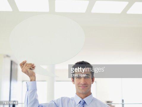 Businessman holding word balloon : Stock Photo