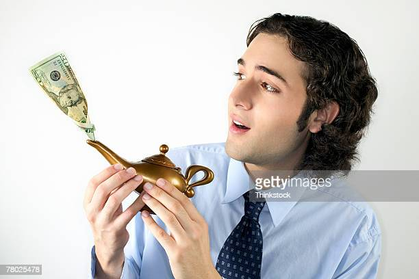 A businessman holds a genie's lamp with money coming out of the spout