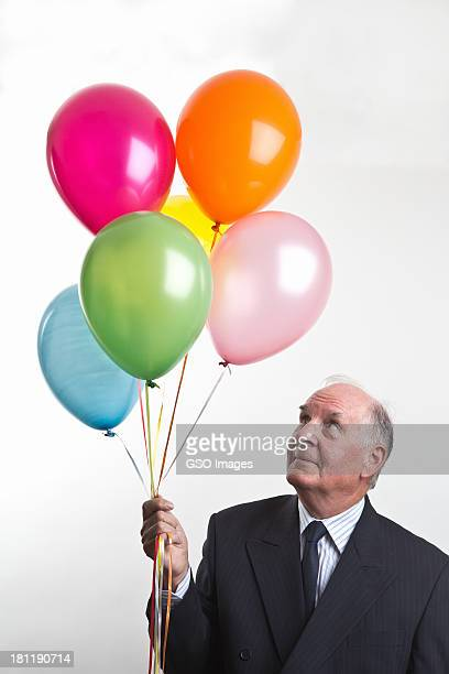 Businessman holds balloons