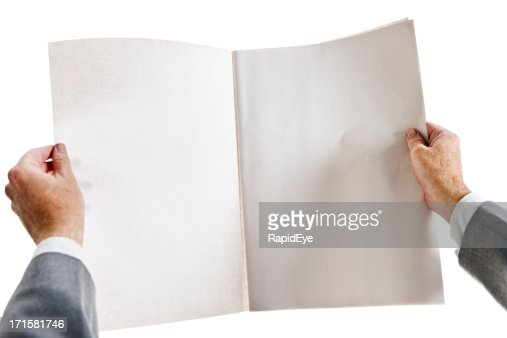 Businessman holds blank newspaper open to centre spread.