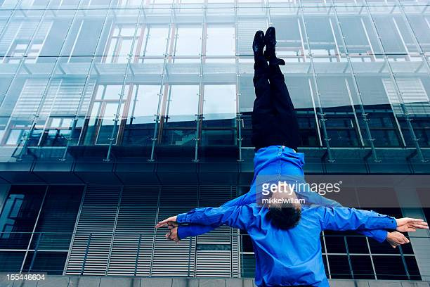 Businessman holds colleague upside down in front of office building