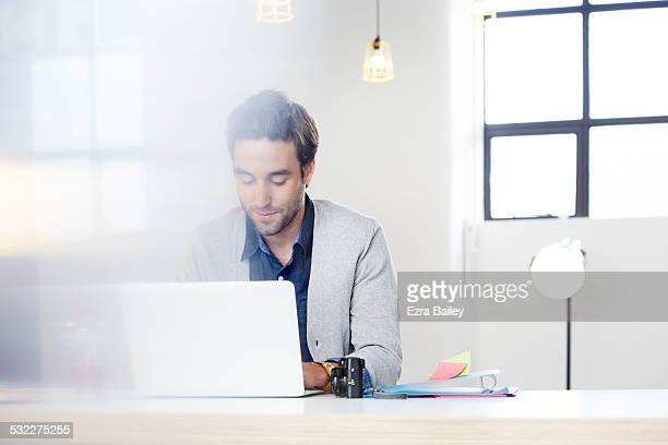 businessman hot-desking in an open plan office.