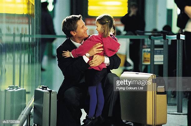 Businessman hugging child at airport