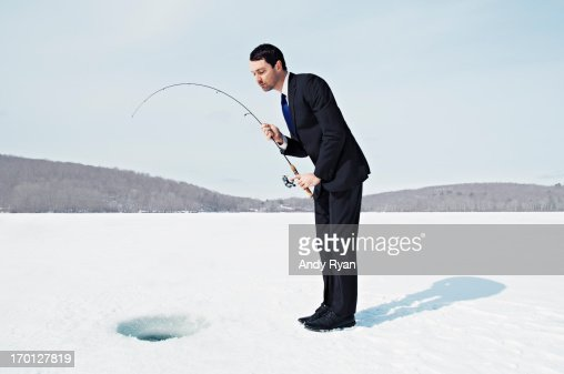 Businessman Ice Fishing on Frozen Lake. : Foto de stock