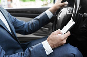 Businessman ignoring safety, texting on smartphone and driving car, cropped