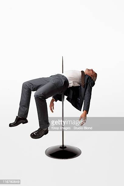 A businessman impaled on a spindle
