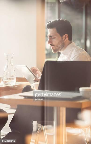 Uomo d'affari in una caffetteria, al lavoro