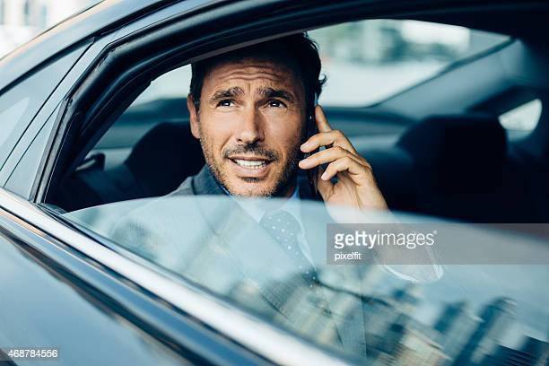 Businessman in a car talking on the phone