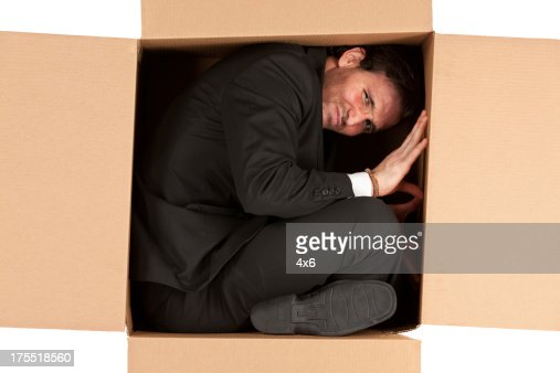 Businessman in a cardboard box