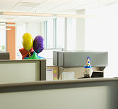 Businessman in a cubicle with a party hat on and a bunch of balloons, Redwood City, California, United States