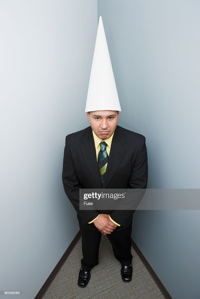 Businessman in a dunce cap : Stock Photo