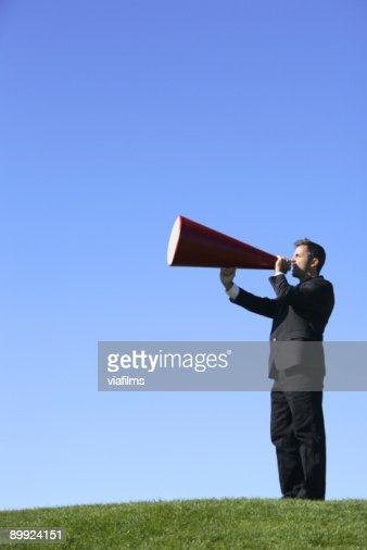 A businessman in a field with a megaphone : Stock Photo