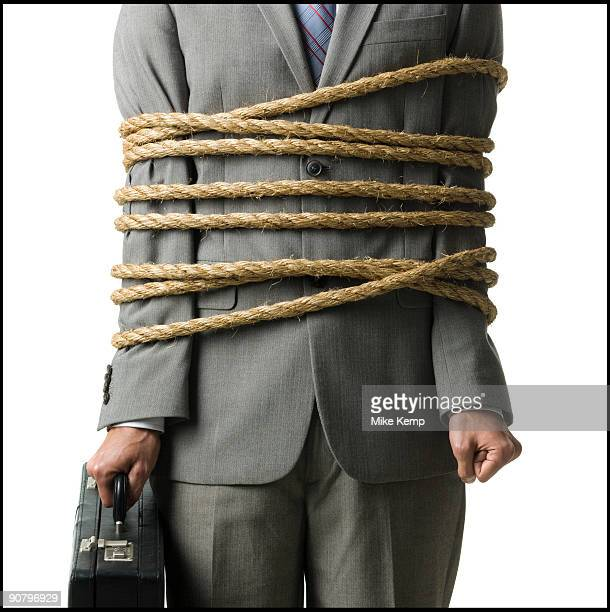 businessman in a full suit tied up with a rope around his mid section