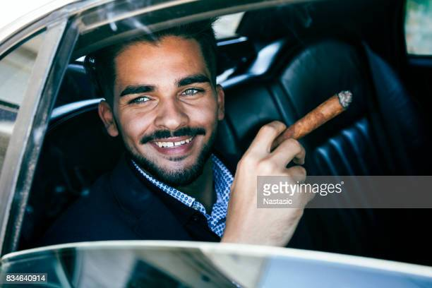 Homme d'affaires dans un cigare de fumer limousine