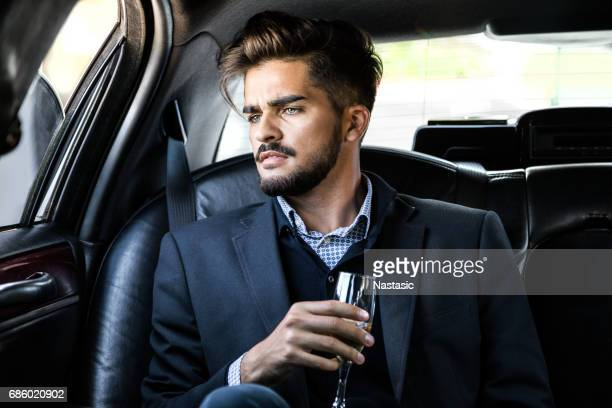 Businessman in a limousine with champagne