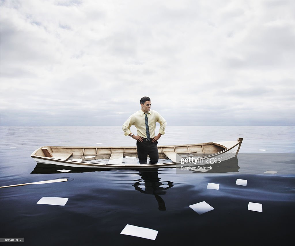 businessman in a sinking boat : Stock Photo