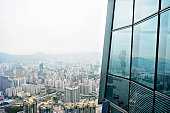 Businesswoman standing in a skyscraper building viewing over the city.