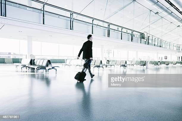 Businessman in a suit walks in airport terminal