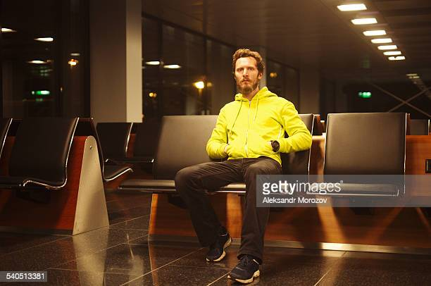 Businessman in airport waiting area using mobile p