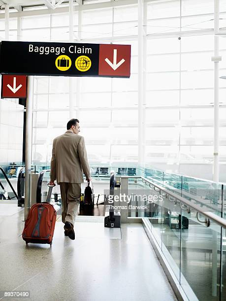 Businessman in airport walking with carry on