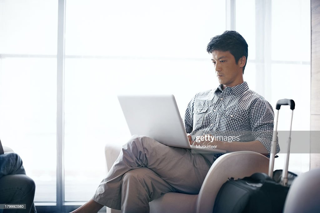 businessman in an airport lounge with laptop