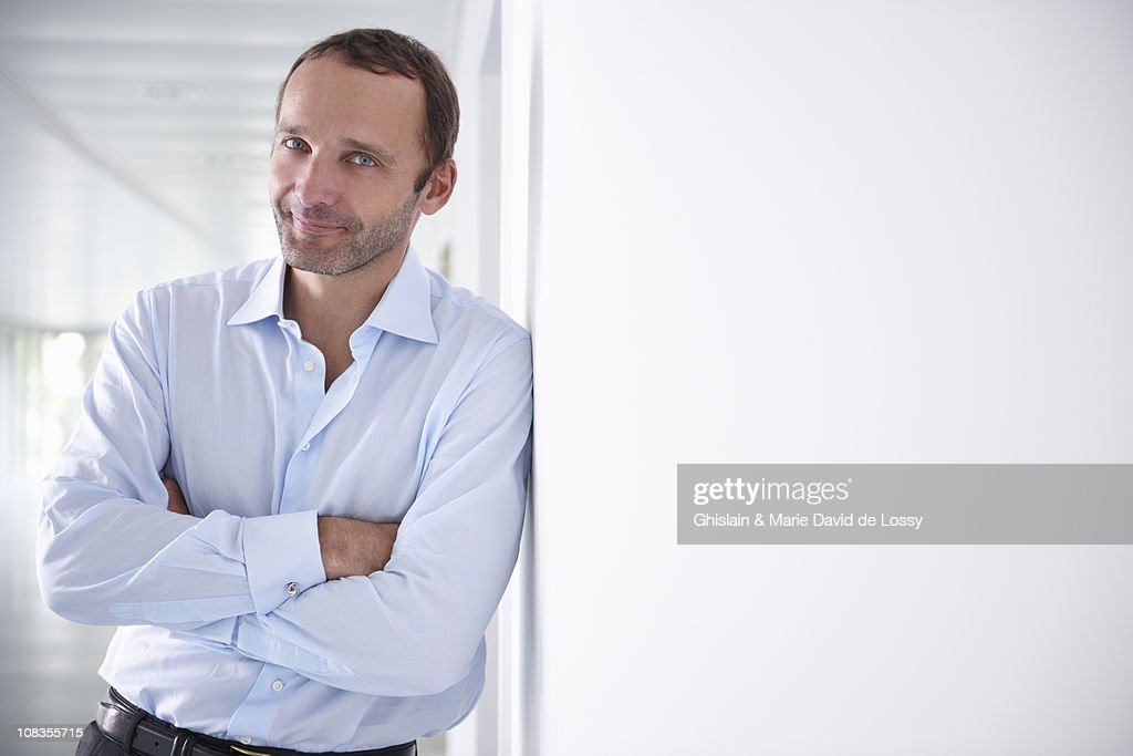 Businessman in an empty office, smiling : Stock Photo