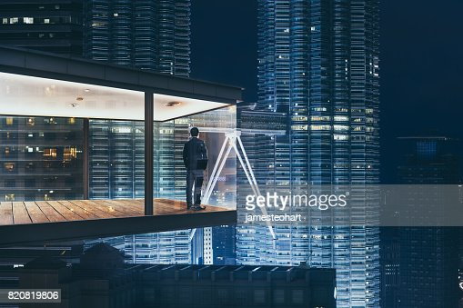 Businessman in an modern sky office by night with beautiful city skyline view . : Foto de stock