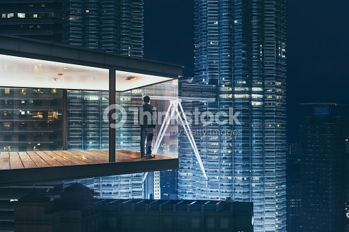 Businessman in an modern sky office by night with beautiful city skyline view . : Stock Photo