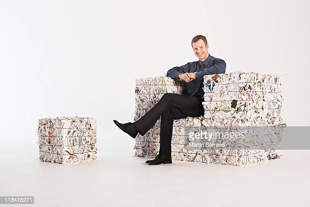 Businessman in armchair made of paper bales