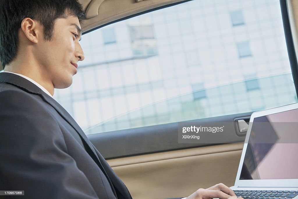 Businessman in Back Seat of Car Typing on Laptop, Low Angle View : Stock Photo